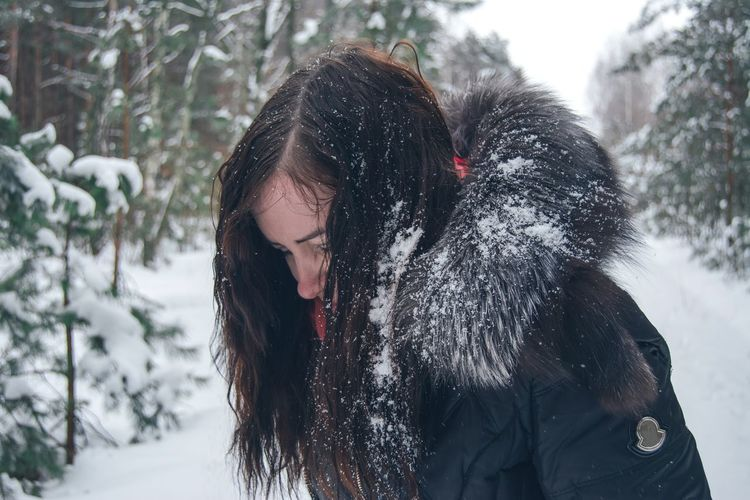 Woman Wearing Warm Clothing In Forest During Winter