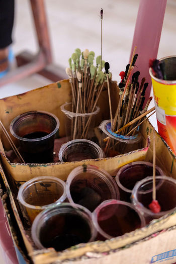 High angle view paintbrushes in disposable cup in box