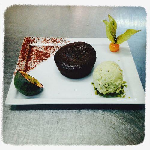 Moelleux au chocolat, boule de glace pistache sur lit de pistache concassées et fruits exotiques Cuisine