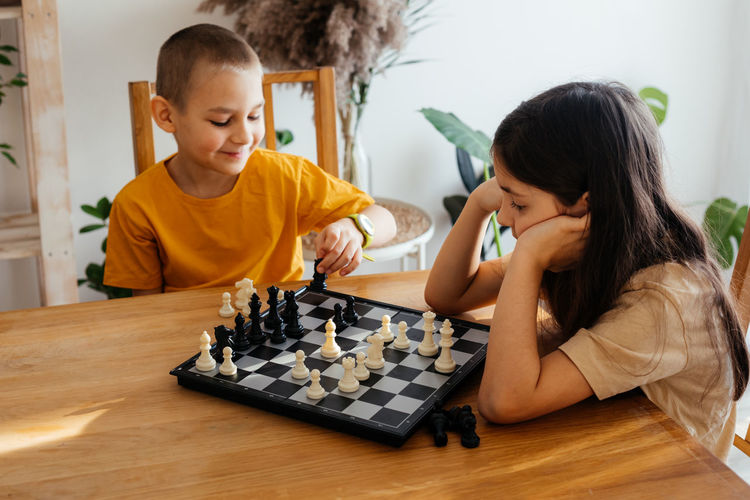 Happy boy playing on a chess board
