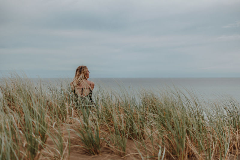 Woman standing on grass by sea against sky