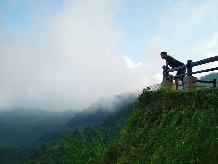 Man Leaning On Railing While Standing At Mountain Peak Against Sky