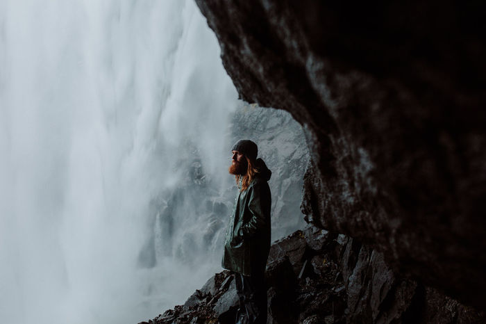 Side view of man standing on cliff against waterfall