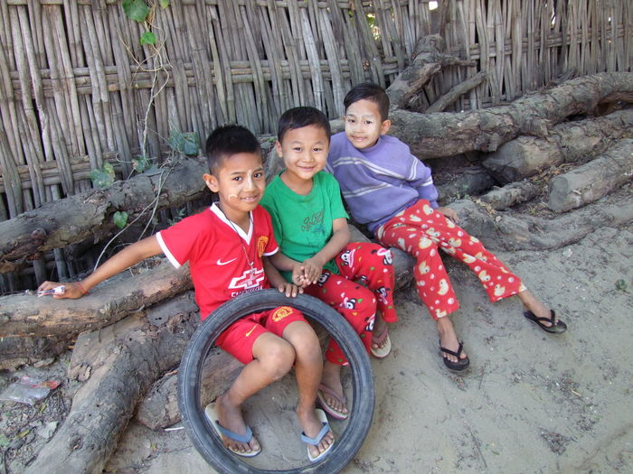 Three Happy Boys in Tanyaung Village Boys Cheerful Child Portrait Childhood Children Playing Children Portrait Composition Daylight Full Frame Full Length Fun Happiness Leisure Activity Looking At Camera Multi Coloured Myanmar Outdoor Photography Portrait Relaxed Atmosphere Smiling Faces Tanyaung Village Three Boys Three Children Togetherness Tyre