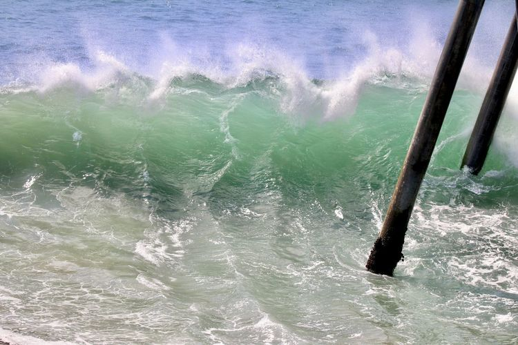 wave crashing under a pier Water Sea Motion Wave Nature Sport Day Beauty In Nature Waterfront No People Outdoors Aquatic Sport Power In Nature Power Scenics - Nature Splashing High Angle View Land Turquoise Colored Breaking