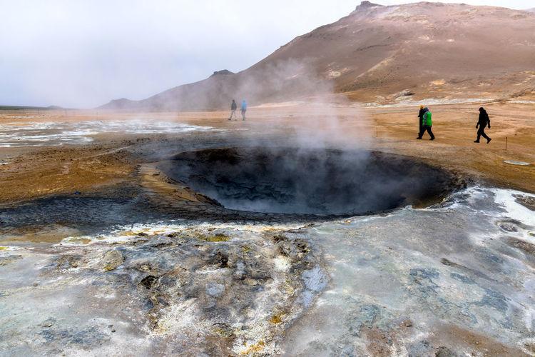 Tourist Walking By Mud Pots At Hverir Against Sky