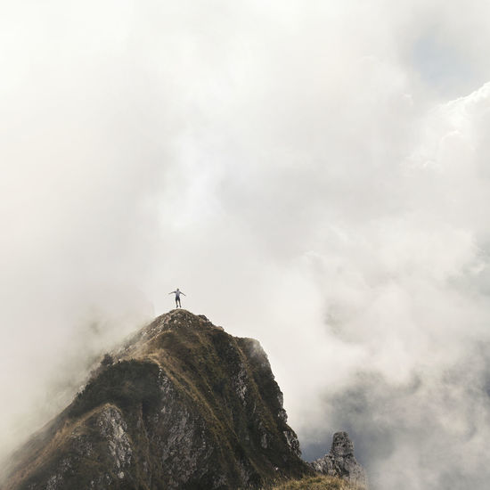 Distant View Of Man Jumping Over Mountain In Foggy Weather