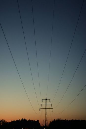 Low angle view of electricity pylon against sky at sunset