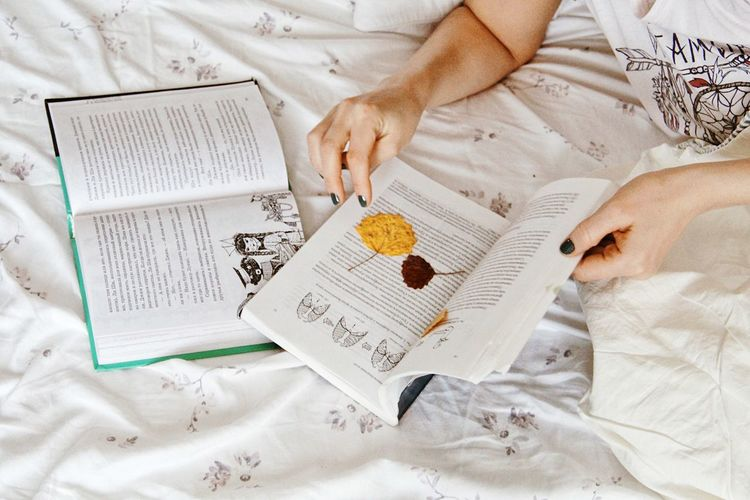 Relaxation Bed Human Hand High Angle View Hand Indoors  Furniture One Person Relaxation Close-up Lifestyles Sheet Holding Pattern Textile Book Paper Floral Pattern Human Body Part Publication Text