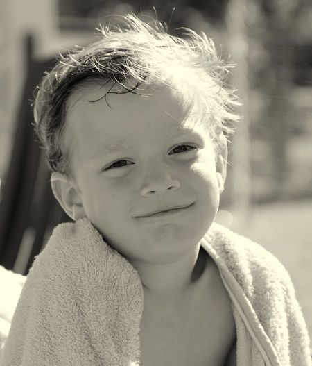 Close-Up Portrait Of Smiling Boy In Beach Towel