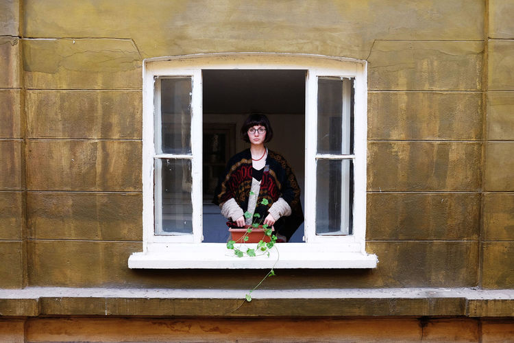 Portrait of woman standing in window