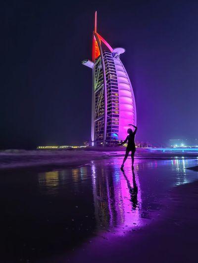 Full length of man standing on illuminated city at night