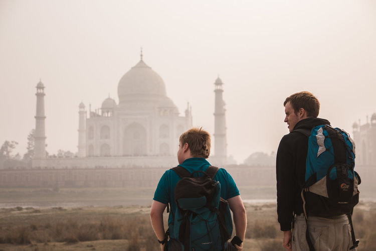 Rear view of tourists carrying backpacks while standing in front of taj mahal during foggy weather