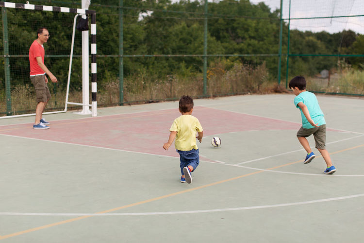 Father and sons playing football 2-3 Years 35-39 Years 6-7 Years Active Lifestyle  Ball Bonding Boys Casual Clothing Childhood Cute Day Enjoyment Family With Two Children Football Full Length Fun Leisure Activity Lifestyles Outdoor Outdoors Playing Rear View Running