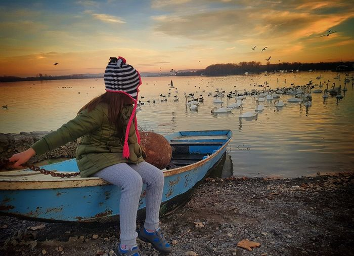 Man sitting on boat moored at beach against sky during sunset