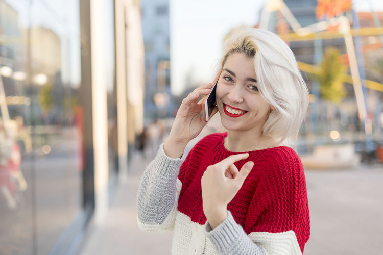 Portrait of cheerful young woman talking on smartphone outdoors. Blonde Calling Happy Attractive Communication Hapinness Happiness Mobile Phone One Person One Woman Only One Young Woman Only Outdoors Selfies Smart Phone Smile Smiling Smiling Face Talking Using Phone Wireless Technology Young Adult Young Women
