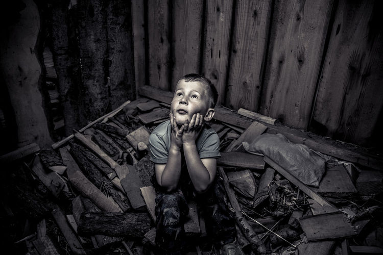 High angle view of frightened boy looking up in abandoned room