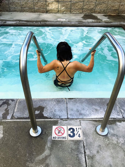 Asian girl getting into jacuzzi on a cloudy day