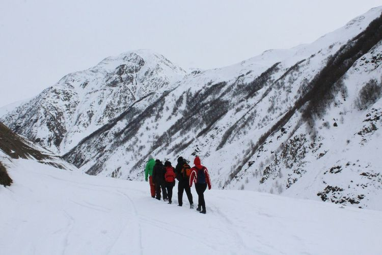 Rear view of people walking on snowcapped mountain
