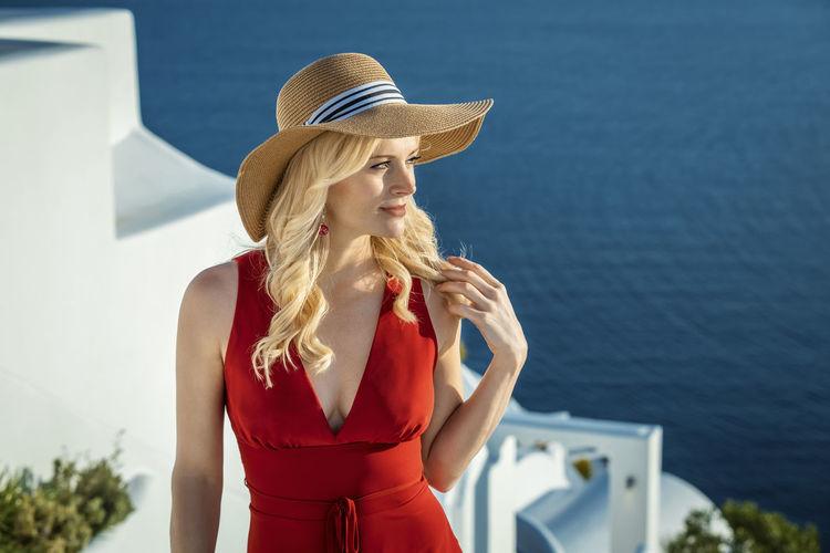 Woman wearing hat standing against sea