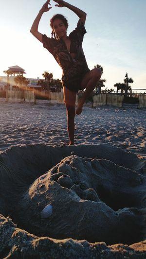 Full length of woman exercising at beach