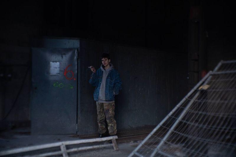 Full length of man smoking cigarette in abandoned room