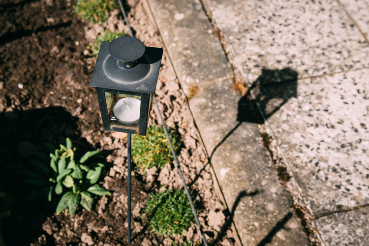 Black Color Clothing Day Field Focus On Foreground Footpath Growth Hat High Angle View Lamp Land Leaf Lighting Equipment Nature No People Outdoors Plant Shadow Solid Street Sunlight