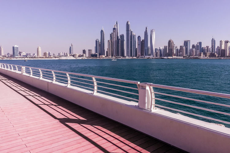 Bridge by sea and urban skyline