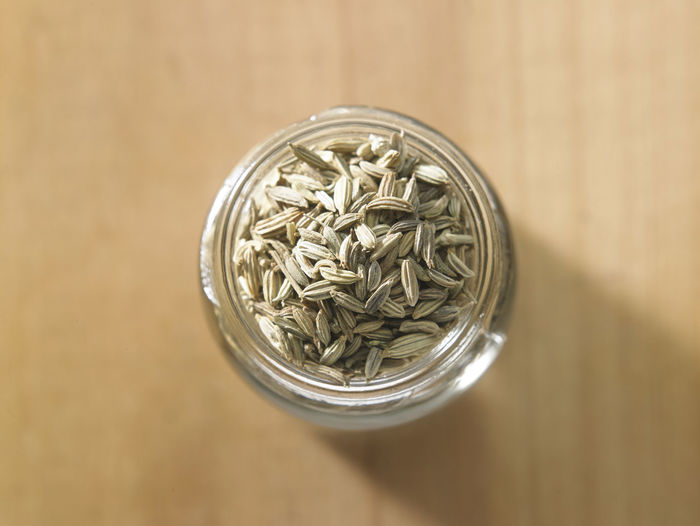 close up of the cumin seeds Spice Seed Cumin Ingredient Medicine Seasoning Scented Aromatic Food Food And Drink Indian Food Condiment Healthy Eating Dried Food Flavor No People Container Jar Glass Still Life Close-up Directly Above Glass - Material Wood Heap