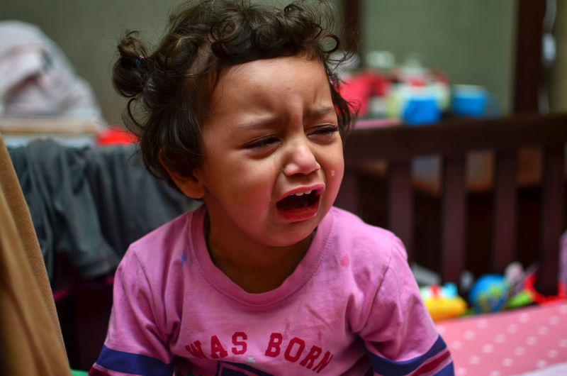 Close-Up Of Girl Crying While Sitting At Home