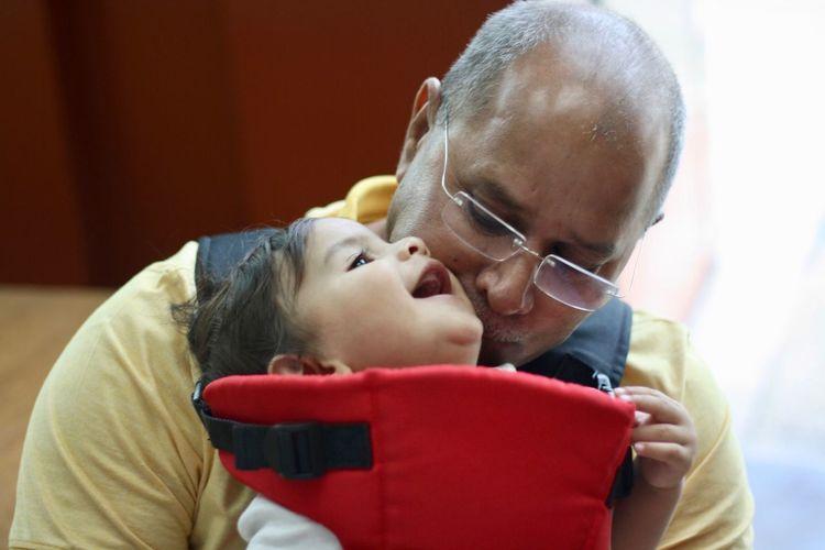Grandfather kissing cute baby boy