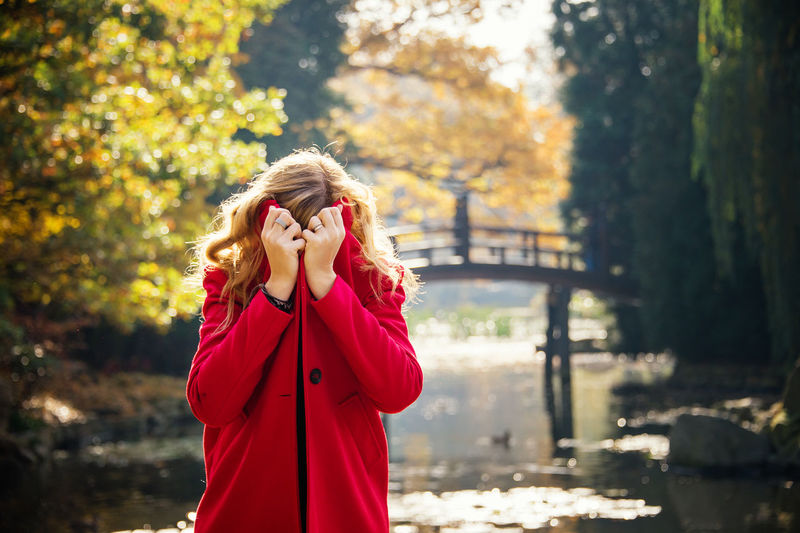 Young woman hiding under red coat in autumn city park near lake