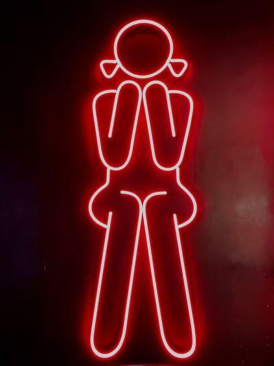 Close-up of illuminated restroom sign