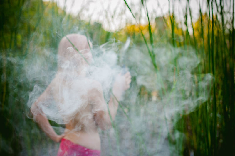 Rear View Of Shirtless Young Woman Smoking While Standing On Grassy Field