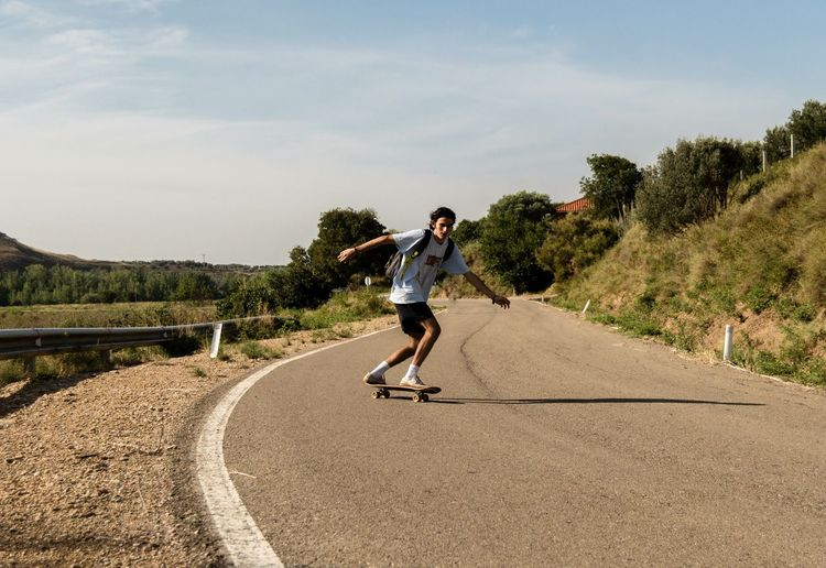 Full length of man skateboarding on road against sky