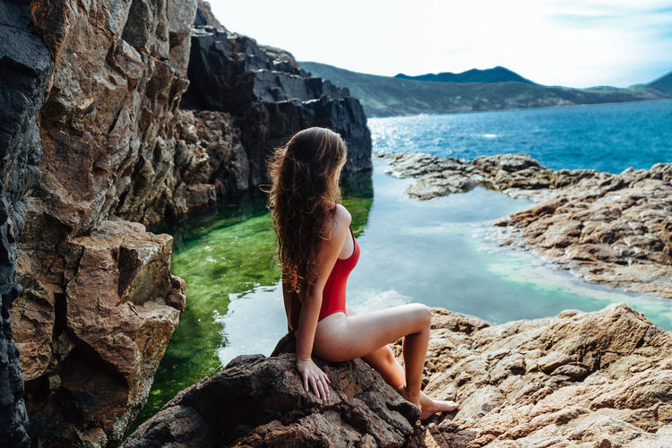Side view of seductive woman wearing swimsuit while sitting on rock by sea