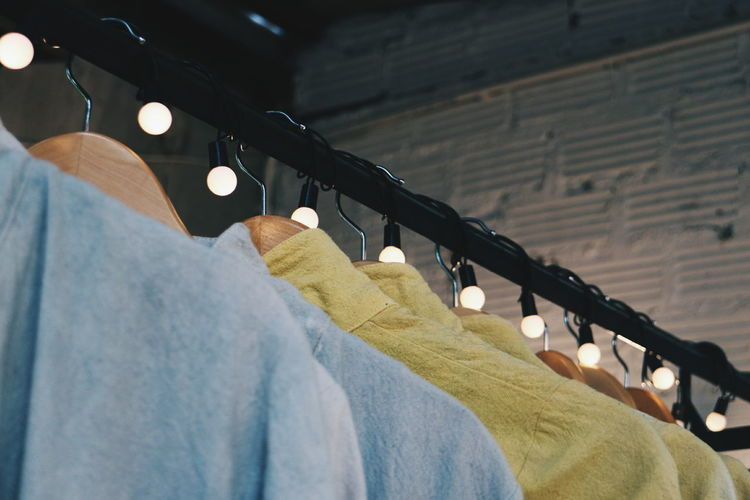 Close-up of clothes hanging on illuminated rack