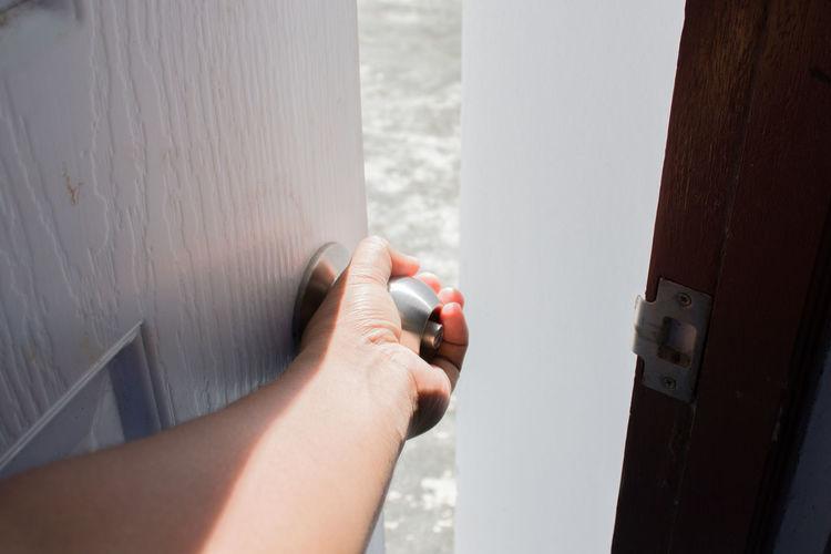 Close-up of hand holding open door