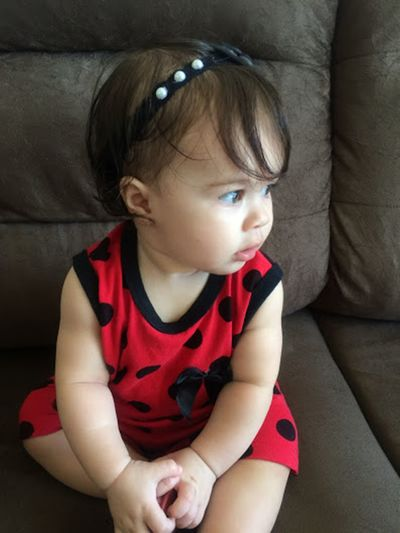 Cute baby girl sitting on sofa at home