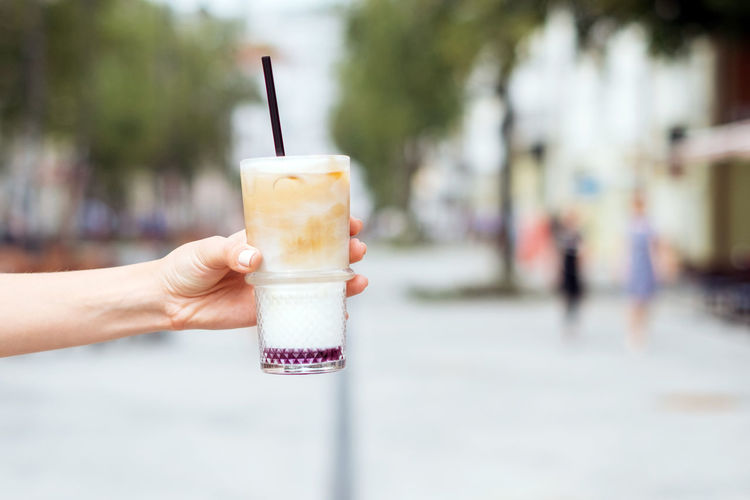 Woman hand holding iced latte Latte City Coffee Mood Dairy Product Day Drink Drinking Glass Drinking Straw Focus On Foreground Food Food And Drink Glass Hand Holding Human Body Part Human Hand One Person Refreshment Straw