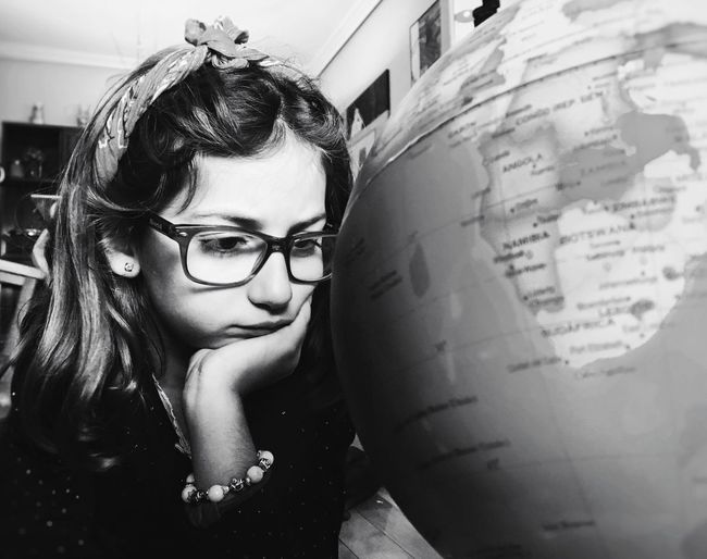 Close-up of little girl looking at globe