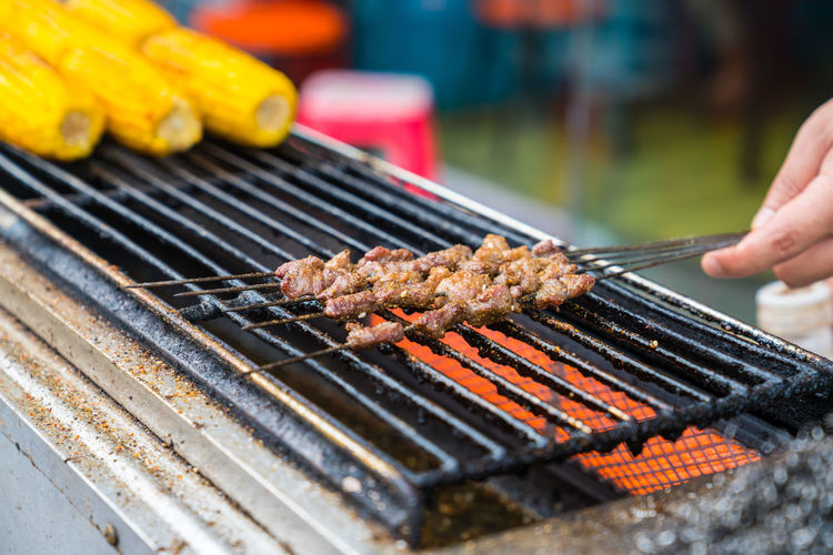 Cropped hand roasting meat on barbecue grill