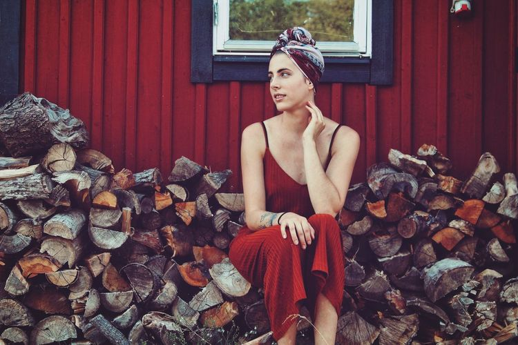 Young woman sitting on logs