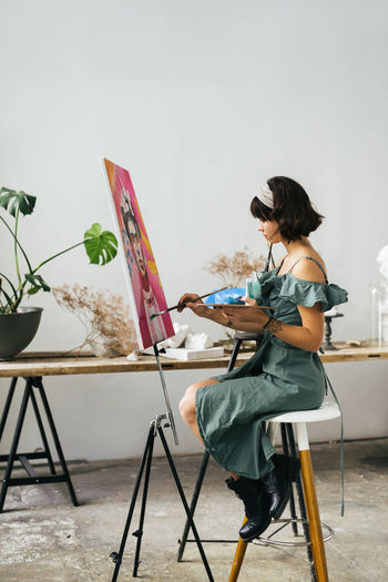 Full length side view of woman painting on canvas at art studio