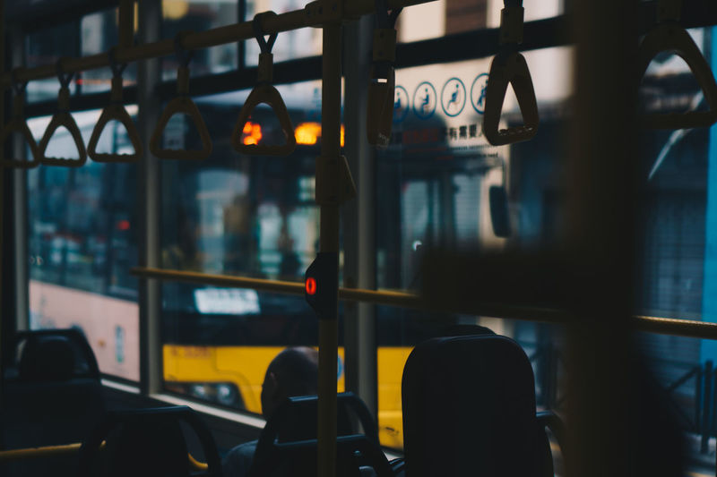 Man sitting on vehicle seat by window in bus