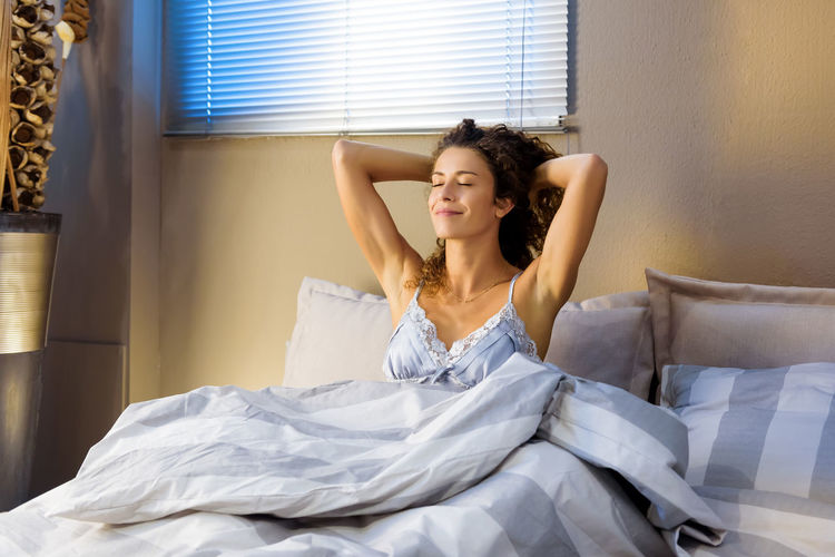 Smiling young woman sitting on bed at home
