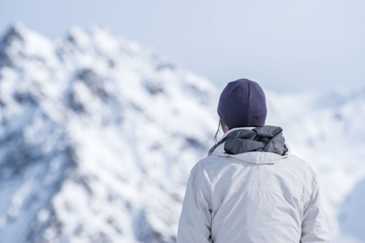 Rear View Of Man In Warm Clothing Standing Against Snowcapped Mountain