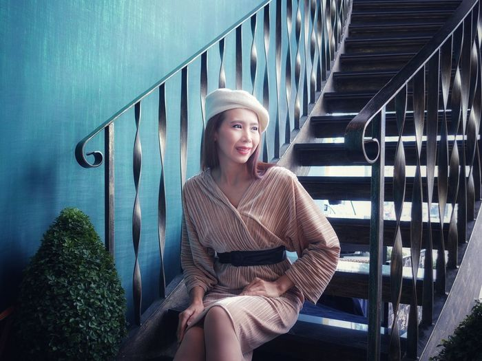 Smiling young woman sitting staircase against railing