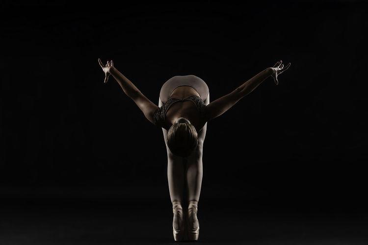 Ballet dancer stretching exercising against black background
