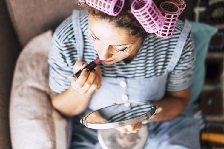 High angle view of woman applying lipstick